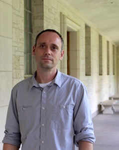 Image of Casey Boyle, standing in an outside corridor wearing a grey, long-sleeved shirt.