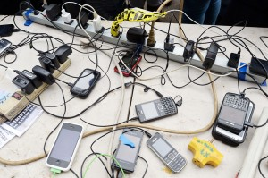 A photograph of a electrical outlet strip with many phones plugged in.