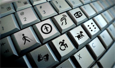 Angled shot of a Keyboard with Accessible Icons in place of letters, icons include those for signs, motion chair, service dog, CC symbol, braille symbol